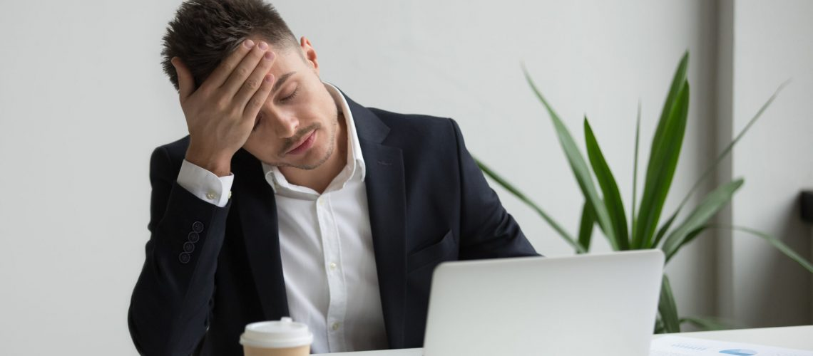 Frustrated fatigued millennial businessman having strong headache tired from laptop use touching forehead, stressed overworked company ceo suffers from migraine at work, aching head in office concept