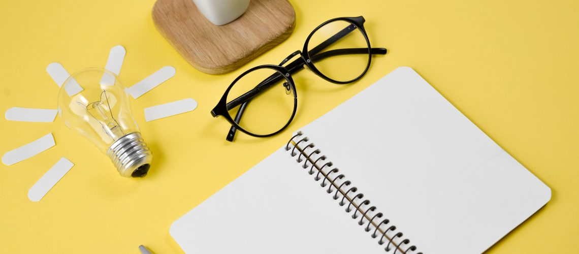 Top view flat lay of workspace desk styled design office supplies with pen, notepad, eyeglasses, cup coffee and light bulb on a yellow color paper background minimal style. Concept brainstorming